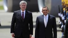 Canada's Prime Minister Stephen Harper (L) walks with Honduras' President Porfirio Lobo as he arrives for an official visit, at the Armando Escalon military base in San Pedro Sula August 12, 2011. (REUTERS/Edgard Garrido/REUTERS/Edgard Garrido)