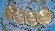 Canadian dollar coins, or Loonies, are displayed on a map of North America on Jan. 9, 2014, in Montreal. (Paul Chiasson/The Canadian Press)