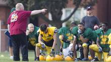 Toronto Mayor Rob Ford, left, coaches the Don Bosco Eagles at practice on Tuesday with his office assistant, Andrew Gillis, back right. (Peter Power/The Globe and Mail)