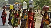 Indian women and children carry drinking water on Himmatnagar Highway, about 60 kilometers north of Ahmadabad, India. (Ajit Solanki/AP)