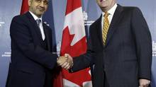 Canada's Foreign Minister John Baird, right, shakes hands with the United Arab Emirates' Ambassador to Canada Mohammed Saif Helal Al Shehhi after making a statement at the Lester B. Pearson Building in Ottawa May 28, 2013. (CHRIS WATTIE/REUTERS)