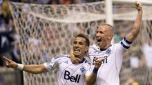 Vancouver Whitecaps FC Camilo Sanvezzo, left, celebrates his goal with teammate Kenny Miller during the first half against Chivas USA during first half of MLS soccer action in Vancouver, Wednesday, June, 19, 2013. (The Canadian Press)