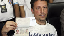 Italian Luigi Maraldi, left, whose stolen passport was used by a passenger boarding a missing Malaysian airliner, shows his passport as he reports himself to Thai police at Phuket police station in Phuket province, southern Thailand Sunday, March 9, 2014. Maraldi spoke at a police news conference where he showed his current passport, which replaced the stolen one, and expressed surprise that anyone could use his old one. (Krissada Muanhawang/AP Photo)