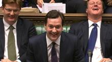 Britain's Chancellor of the Exchequer George Osborne, centre, with Treasury Secretary Danny Alexander, left, and Prime Minister David Cameron after delivering his autumn budget in parliament on Dec. 5, 2012. (Reuters)