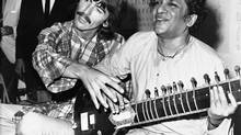 In this Aug. 3, 1967 file photo, George Harrison, of the Beatles, left, sits cross-legged with his musical mentor, Ravi Shankar of India, in Los Angeles, as Harrison explains to newsmen that Shankar is teaching him to play the sitar. (Uncredited/AP)