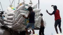 Workers unload 42,494 tonnes of Thai rice at the Tanjung Priok harbour in Jakarta January 25, 2011. (CRACK PALINGGI/Crack Palinggi/Reuters)