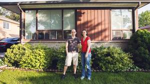 Anthony Jones and Meredith Greenfield in front of their house as it looks before renovations, which include adding another floor.
