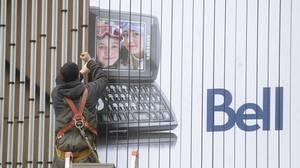A worker assembles a Bell Canada billboard