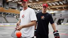 Eric Staal, left, from Thunder Bay, Ont., balance a ball on his stick as his brother Marc Staal, from Thunder Bay, Ont., looks on following a ball hockey training session at the Canadian national men's team orientation camp in Calgary, Alta., Tuesday, Aug. 27, 2013. (Jeff McIntosh/THE CANADIAN PRESS)