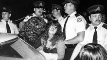 Rock fans trying to get into Ontario Place to see Teenage Head. Toronto police force the fans against cruiser as mounted officers herded crowds across the bridge from Ontario Place to the CNE grounds, June 2, 1980. Originally published June 3, 1980, page A1 (Barrie Davis/The Globe and Mail)
