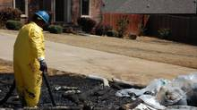 A member of a cleanup crew works in Mayflower, Ark., on Monday, April 1, 2013, days after a pipeline ruptured and spewed oil over lawns and roadways. (Jeannie Nuss/AP)