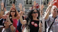 Civil service workers raise their arms during a protest against government austerity measures outside the Treasury Ministry in Madrid, July 13, 2012. (PAUL HANNA/REUTERS)