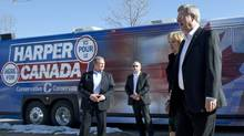 Prime Minister Stephen Harper and Laureen Harper step off the campaign bus as they stop in Brampton, Ont., on March 30, 2011. (Adrian Wyld/THE CANADIAN PRESS)