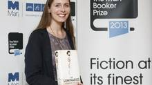 """Man Booker prize shortlist nominee Eleanor Catton poses with her book """"The Luminaries"""" at the Southbank Centre in London, Oct. 13, 2013. (OLIVIA HARRIS/REUTERS)"""