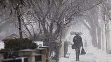 A man walks down the street duringsnowfall in Toronto, Wednesday, March 12, 2014. (Mark Blinch for the Globe and Mail)