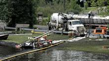 Workers using suction hoses try to clean up an oil spill this week from the Kalamazoo River in Battle Creek, Mich. (Bill Pugliano/2010 Getty Images)