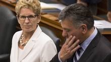 Ontario's Premier Kathleen Wynne, left, sits with Finance Minister Charles Sousa as they attend the Throne Speech at Queens Park in Toronto on Thursday, July 3, 2014. (Chris young/The Canadian Press)