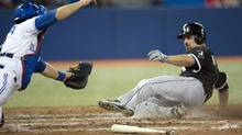 Toronto Blue Jays catcher J.P. Arencibia dives to try to make the tag as Chicago White Sox Paul Konerko slides into home plate for the game winning run during ninth inning AL action in Toronto on Tuesday, April 16, 2013. (Frank Gunn/THE CANADIAN PRESS)