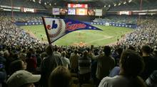 Fans cheers on the Montreal Expos during the team's final home game ever in Montreal against the Florida Marlins at Olympic Stadium, September 29, 2004. (CHRISTINNE MUSCHI/REUTERS)