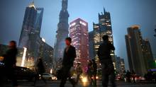 People walk along a busy street at Pudong financial district in Shanghai, March 27, 2013. Emerging markets were in a state of shock after a week in which bonds and currencies got hammered and equities suffered their worst drubbing in more than a year. It was just the latest in a series of setbacks for once high-flying markets like Brazil, India and China, as investors are lured away in droves to rising yields in pockets of the developed world and even some of the higher-risk frontier markets. (CARLOS BARRIA/Reuters)