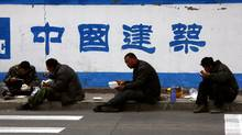 Migrant workers eat their lunch outside a construction site in central Beijing, April 2, 2012. As the number of adults flowing into the workforce slows, China can no longer attract manufacturing with the promise that an unending pool of rural migrants will keep its wages down. (David Gray/Reuters/David Gray/Reuters)