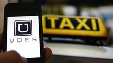 The logo of taxi app Uber is shown next to a German taxi sign in Frankfurt. Toronto Police recently charged at least 11 UberX drivers (KAI PFAFFENBACH/REUTERS)