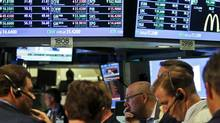 In a July 13, 2012, file photo, traders work as the New York Stock Exchange nears closing. (Bebeto Matthews/AP)