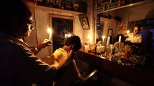 An Indian barber, holding a candle, gives a customer a haircut at his shop in Kolkata, India, on Tuesday after a massive collapse of three of the nation's regional power grids. (Bikas Das/Associated Press)