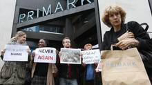 A shopper passes demonstrators outside clothing retailer Primark in central London April 27, 2013. The demonstrators were protesting following the collapse of a building in Bangladesh where low-cost garments were made for Western brands. (SUZANNE PLUNKETT/REUTERS)
