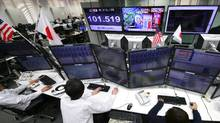 Money traders watch computer screens with the day's exchange rate between yen and the U.S. dollar at a foreign exchange brokerage in Tokyo, Wednesday, Nov. 9, 2016. Asian shares have shed early gains, tumbling Wednesday as Donald Trump gained the lead in the electoral vote count in the presidential election. Dow and S&P futures also plunged. Earlier, investors had appeared persuaded that Hillary Clinton, seen as a more stable choice, would prevail. (Shizuo Kambayashi/The Associated Press)