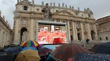 People in Saint Peter's Square watch a live television screen showing cardinals entering the Sistine Chapel to begin the conclave in order to elect a successor to Pope Benedict, at the Vatican March 12, 2013. (GIAMPIERO SPOSITO/REUTERS)