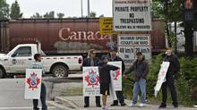Picketers stand at the entrance to the CP Rail yards in Coquitlam, British Columbia May 23, 2012. (ANDY CLARK/REUTERS)