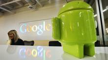 A Google Android figurine sits on the welcome desk as employee Tracy McNeilly smiles at the new Google office in Toronto, November 13, 2012. (MARK BLINCH/REUTERS)