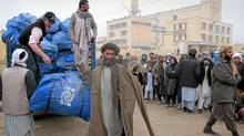 An Afghan wheat farmer Mir Ahmad, a 58-year-old receives a sack containing humanitarian aid donated by International Organization for Migration (IOM) for drought-hit families in Mazar-e-Sharif, Balkh province, north of Kabul, Afghanistan. (Deb Riechmann/Associated Press/Deb Riechmann/Associated Press)