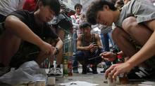 Two men watch their fighting crickets at an insect market in Beijing. (KIM KYUNG-HOON/REUTERS)