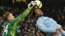Manchester United's Anders Lindegaard, left, clears the ball from the head of Manchester City's Joleon Lescott during their FA Cup soccer match. (PHIL NOBLE/Reuters)