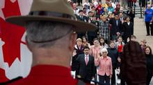 A Royal Canadian Mounted Police officer raises his hand as a group of 60 people take the oath of citizenship during a special Canada Day citizenship ceremony in Vancouver, B.C., on Sunday July 1, 2012. (DARRYL DYCK/The Canadian Press)