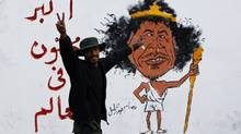 A Libyan man gestures front of a graffiti reading: 'The greatest Crazy of the World' Friday in Tripoli. The death Thursday of Moammar Gadhafi, two months after he was driven from power and into hiding, decisively buries the nearly 42-year regime that had turned the oil-rich country into an international pariah and his own personal fiefdom. AP Photo/Francois Mori (Francois Mori/AP)