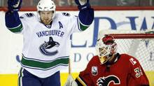 Vancouver Canucks' Henrik Sedin, left, from Sweden, celebrates teammate Mikael Samuelsson's goal as Calgary Flames goalie Miikka Kiprusoff, from Finland, sweeps the puck out of the net during third period NHL hockey action in Calgary, Friday, Oct. 16, 2009. The Calgary Flames beat the Vancouver Canucks 5-3. THE CANADIAN PRESS/Jeff McIntosh (Jeff McIntosh/THE CANADIAN PRESS)