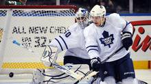 Caption: Toronto Maple Leafs goaltender Jonas Gustavsson (L) looks down to the puck as defenseman Luke Schenn defends during first period NHL hockey action against the Buffalo Sabres in Buffalo, New York, October 30, 2009. REUTERS/Gary Wiepert (GARY WIEPERT)