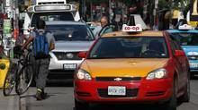 A man ways his way to his illegally parked vehicle during rush hour on King Street as cyclists and other vehicles manoeuvre around his car in Toronto, Ontario, Canada. (Deborah Baic/Deborah Baic/The Globe and Mail)