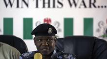 Nigerian police spokesman Frank Mba speaks in front of a poster reading 'win this war' at a news conference in Abuja May 19, 2014. (Joe Penney/Reuters)