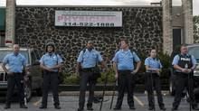 Police officers stand guard in front of a building during protests against the shooting death of Michael Brown, in Ferguson, Missouri, August 17, 2014. U.S. Attorney General Eric Holder ordered a federal autopsy of the teenager, seeking to assure the family and community there will be a thorough investigation into a death that has sparked days of racially charged protests. (Reuters)