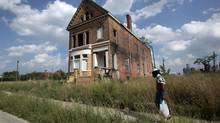 A man walks past a boarded-up home near downtown Detroit, Michigan, on July 19, 2013. Investors dumped Detroit's municipal bonds a day after the city's historic bankruptcy filing even as a ruling in state court raised questions about whether the bankruptcy will stand up to court review. (REBECCA COOK/REUTERS)