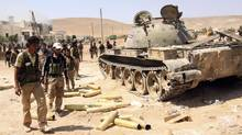 Free Syrian Army fighters inspect munitions and a tank that belonged to forces loyal to Syria's President Bashar al-Assad after they seized Aleppo's town of Khanasir on Aug. 26, 2013. (REUTERS)