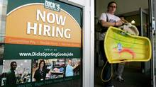 """A customer walks past a """"now hiring"""" poster on the door of a Dick's sporting goods store in in Aurora, Ohio. (Amy Sancetta/AP Photo/Amy Sancetta)"""