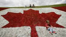 Samuel Rosas celebrates his third birthday (in behind are his cousin Andrea Suarez, aunt Carolina Rosas and father Camilo Rosas), by playing on a giant Canada Flag painted on a hillside at a Canada Day celebration, Wednesday, July 1, 2009, in London, Ontario. Samuel's family came to Canada from Columbia 3 1/2 years ago.THE CANADIAN PRESS/Dave Chidley (DAVE CHIDLEY/Dave Chidley/The Canadian Press)