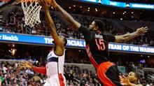 Toronto Raptors forward Amir Johnson, right, blocks a shot by Washington Wizards guard John Wall on Saturday. (Brad Mills/USA Today Sports)