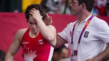 Canada's Martine Dugrenier is consoled by her coach after losing to Mongolia's Battsetseg Soronzonbold in the women's freestyle 63kg weight category at the 2012 Summer Olympics in London, England, Wednesday August 8/2012. (Kevin Van Paassen/The Globe and Mail)