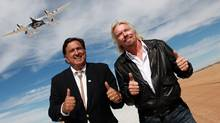 Virgin Galactic's WhiteKnight Two and SpaceShip Two flies over head at the airfield at Spaceport America in Upham, New Mexico as New Mexico Governor Bill Richardson and Sir Richard Branson pose at the runway dedication October 22, 2010 in this publicity photograph. (HO)